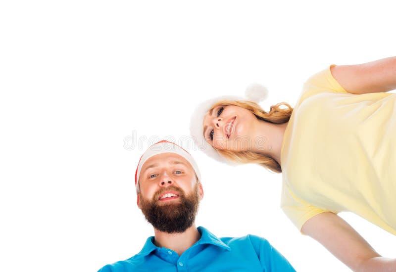 Couples dans des chapeaux de Noël célébrant la nouvelle année ensemble D'isolement photographie stock libre de droits