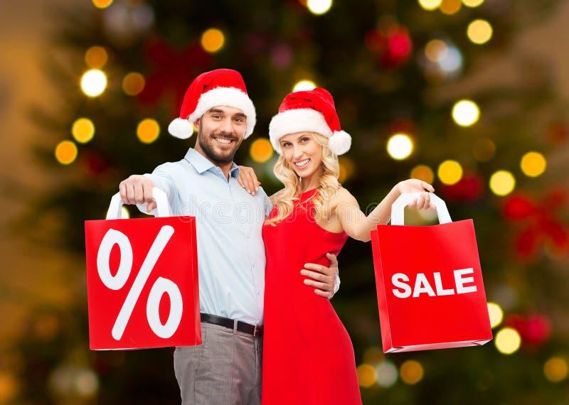 Couples dans des chapeaux de Santa faisant des emplettes sur Noël photographie stock libre de droits