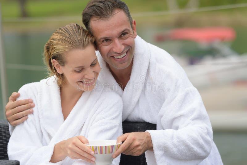 Couples dans des peignoirs partageant la boisson dehors image stock