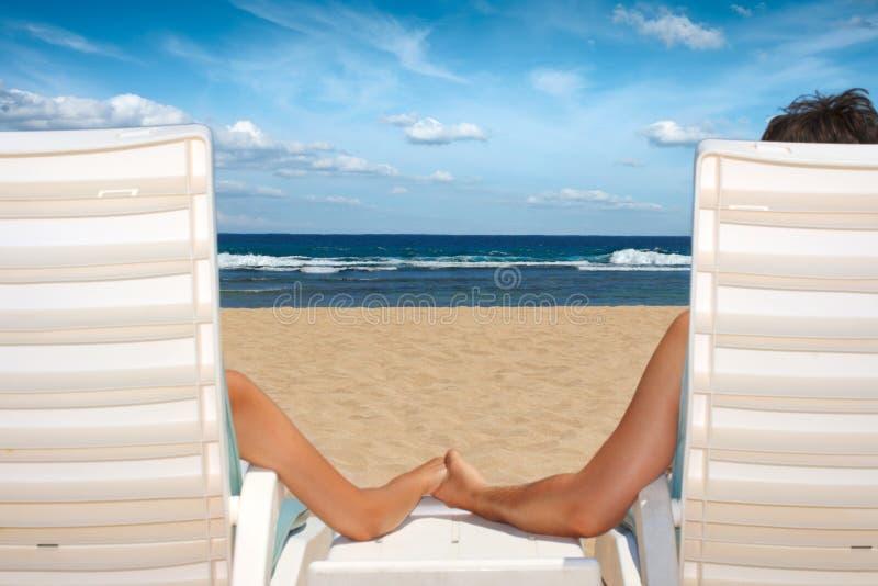 Couples dans des présidences de plage retenant des mains photographie stock libre de droits