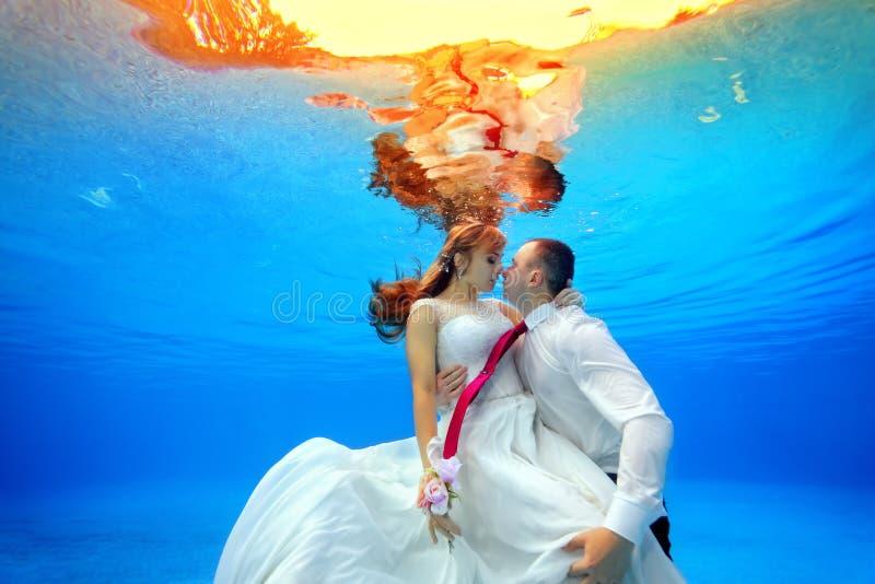 Couples dans des robes de mariage étreignant et embrassant l'eau du fond dans la piscine au coucher du soleil photos stock