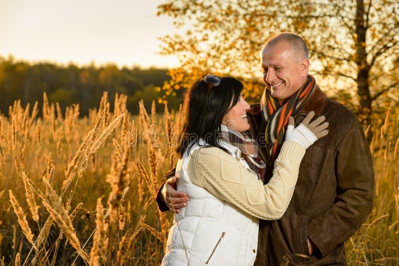Couples dans l'amour étreignant dans le coucher du soleil d'automne image libre de droits