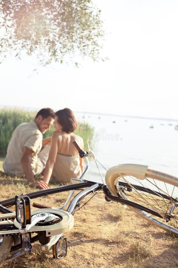 Couples dans l'amour avec la bicyclette flirtant devant le lac photos libres de droits