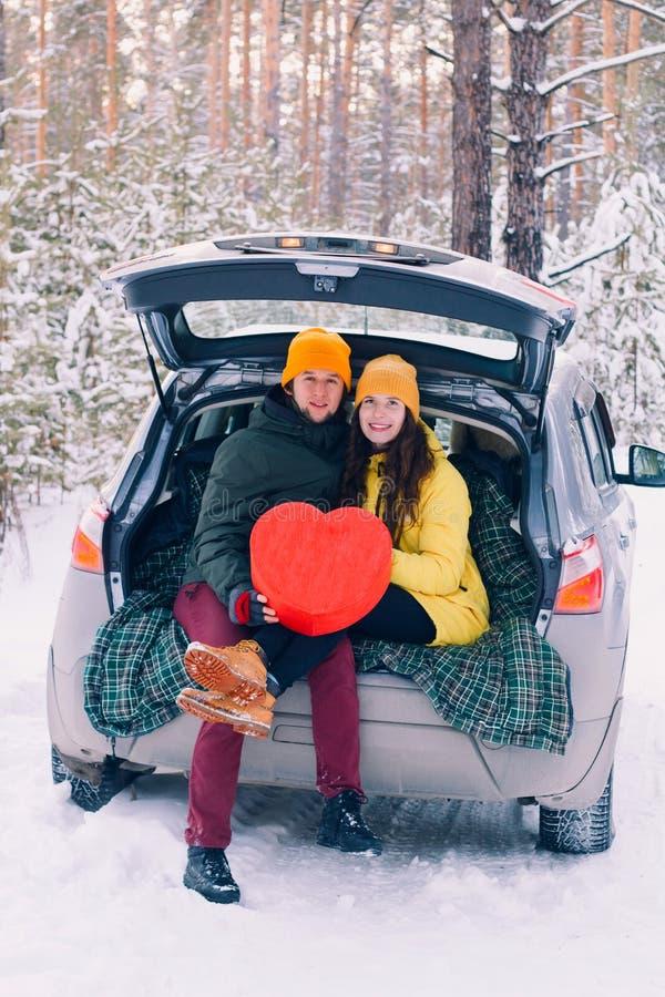Couples dans l'amour avec le grand coeur rouge se reposant dans une voiture photo stock