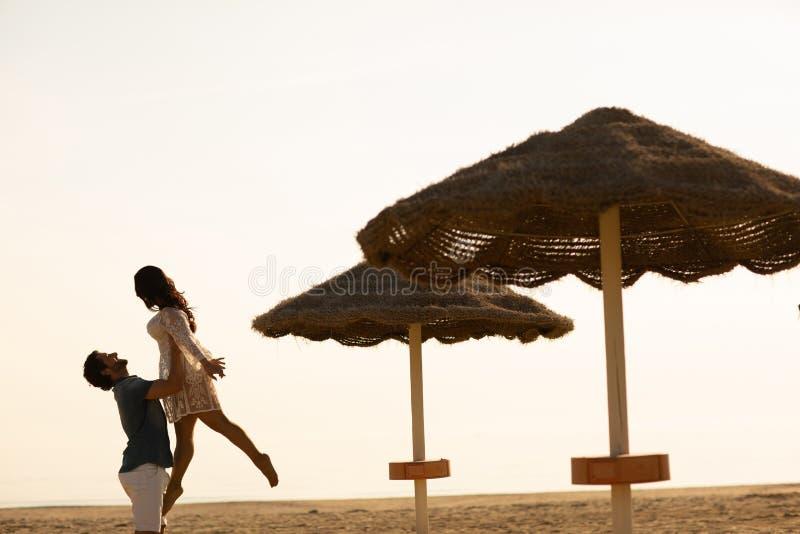Couples dans l'amour ayant des moments tendres romantiques sur la plage près des parapluies en osier Jeunes amants appréciant des photos stock