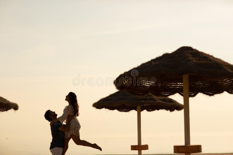 Couples dans l'amour ayant des moments tendres romantiques sur la plage près des parapluies en osier Jeunes amants appréciant des photo stock