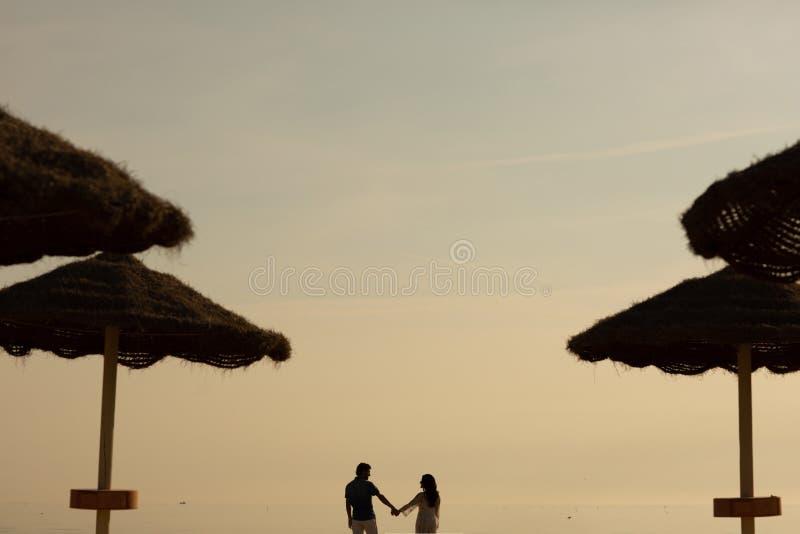 Couples dans l'amour ayant des moments tendres romantiques sur la plage près des parapluies en osier Jeunes amants appréciant des images libres de droits