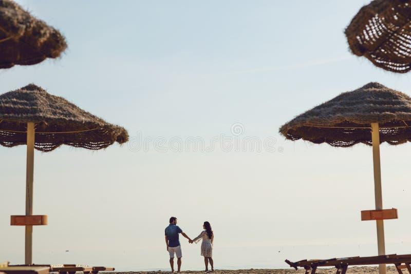 Couples dans l'amour ayant des moments tendres romantiques sur la plage près des parapluies en osier Jeunes amants appréciant des images stock