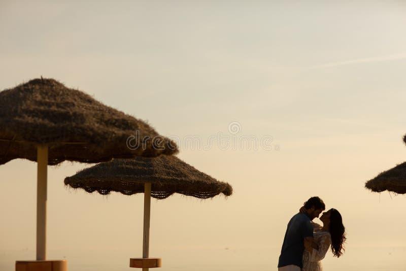 Couples dans l'amour ayant des moments tendres romantiques sur la plage près des parapluies en osier Jeunes amants appréciant des image libre de droits