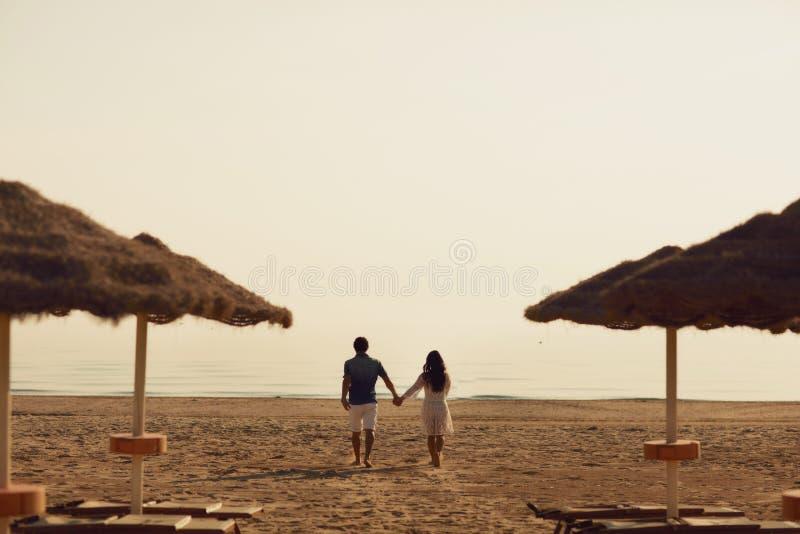 Couples dans l'amour ayant des moments tendres romantiques sur la plage près des parapluies en osier Jeunes amants appréciant des image stock