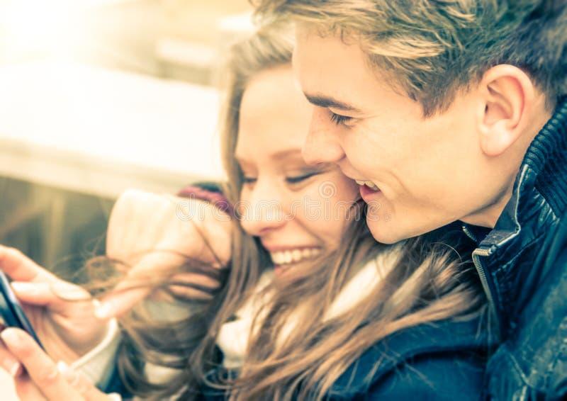 Couples dans l'amour ayant l'amusement avec Smartphone images stock
