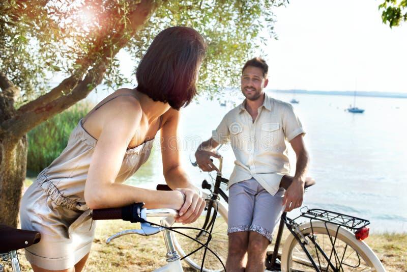 Couples dans l'amour ayant l'amusement en le vélo en vacances au lac image libre de droits