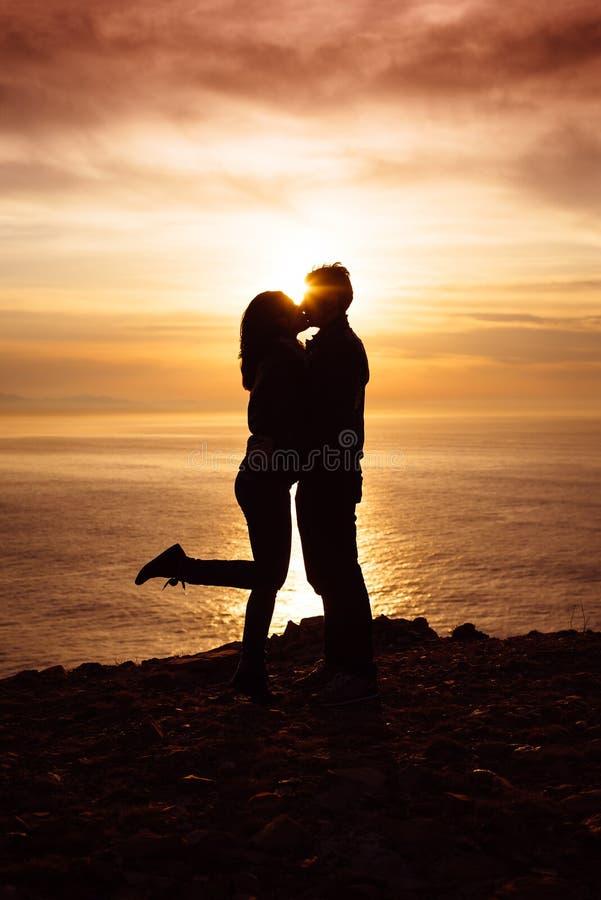 Couples dans l'amour embrassant au coucher du soleil image libre de droits