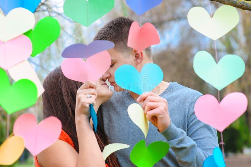 Couples dans l'amour embrassant dans la décoration des coeurs, sur le festin photos libres de droits