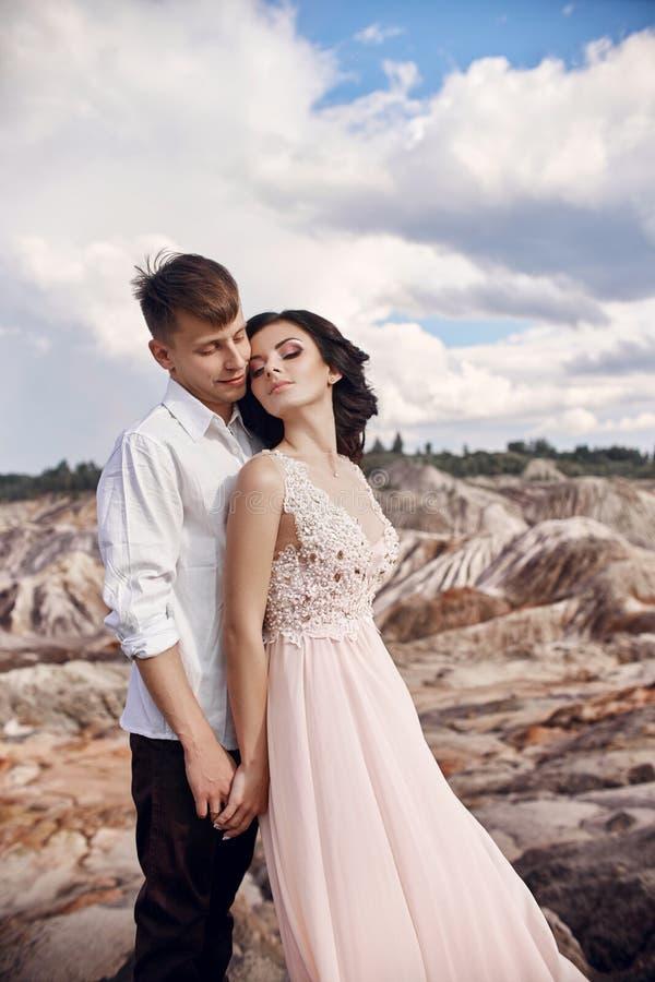Couples dans l'amour en montagnes fabuleuses étreignant, paysage martien photos libres de droits