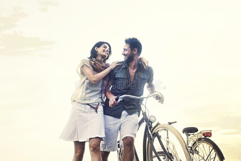 Couples dans l'amour poussant la bicyclette ensemble photo stock