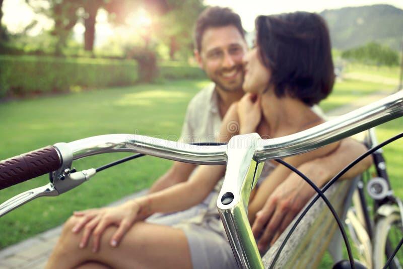 Couples dans l'amour se reposant ensemble sur un banc avec des vélos photos stock