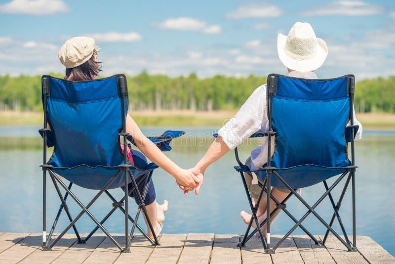 Couples dans l'amour se reposant sur des chaises au pilier près du lac et tenant h photos stock
