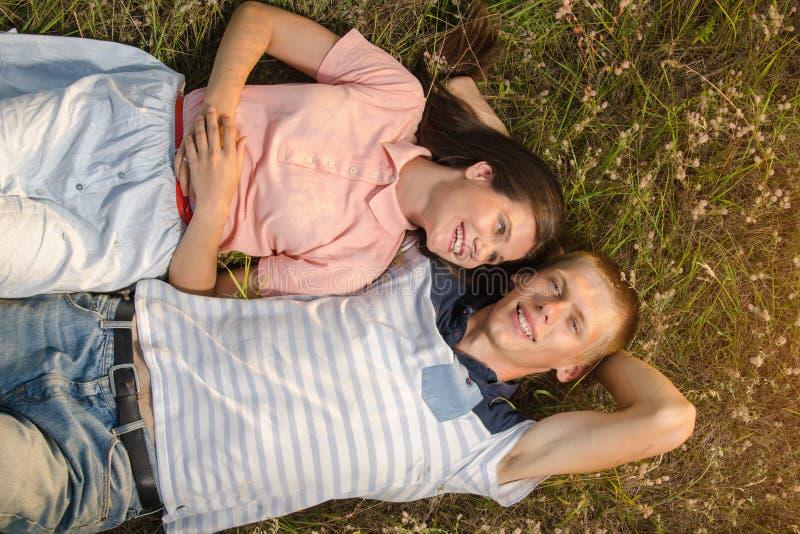 Couples dans l'amour se trouvant sur l'herbe verte image libre de droits