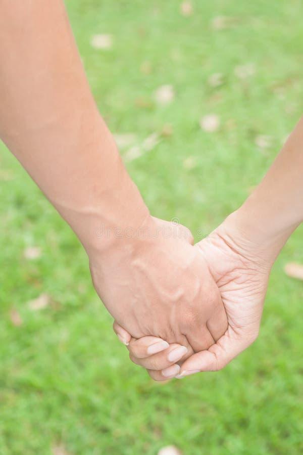 Couples dans l'amour tenant des mains, le betwee d'amitié et de concept d'amour photographie stock