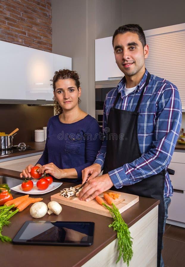 Couples dans la cuisine à la maison prepairing la nourriture saine images stock