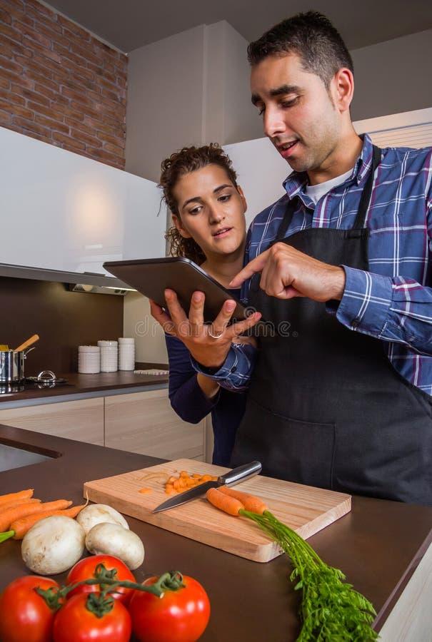 Couples dans la cuisine à la maison regardant la recette avec un comprimé électronique image libre de droits