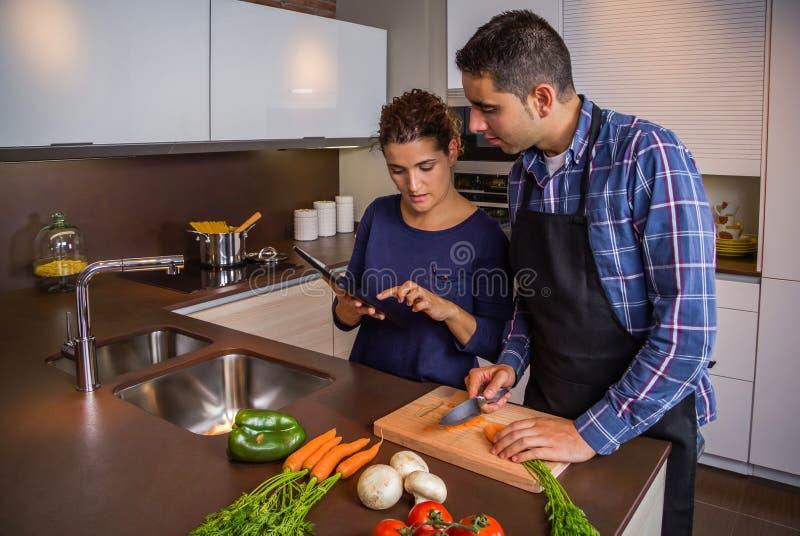 Couples dans la cuisine à la maison regardant la recette avec un comprimé électronique images libres de droits