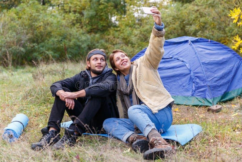 Couples dans la forêt près d'une tente de camping Et photographiant ensemble images libres de droits