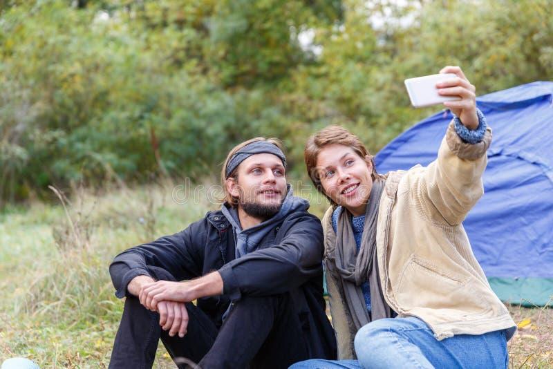 Couples dans la forêt près d'une tente de camping Et photographiant ensemble photo stock
