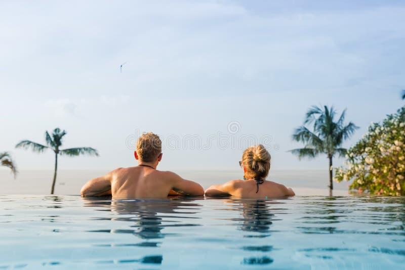 Couples dans la piscine d'infini regardant l'horizon images libres de droits