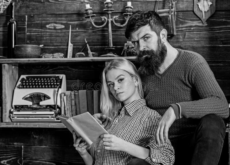 Couples dans la poésie de lecture d'amour en atmosphère chaude Madame et homme avec la barbe sur les visages rêveurs avec le livr photographie stock libre de droits