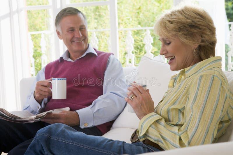 Couples dans la salle de séjour avec du café et le journal photographie stock