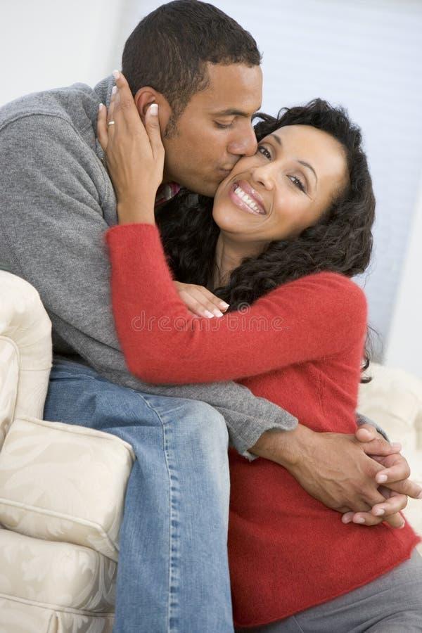 Couples dans la salle de séjour embrassant et souriant photographie stock libre de droits