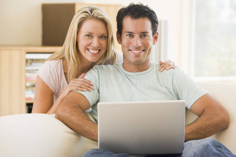 Couples dans la salle de séjour utilisant le sourire d'ordinateur portatif photos stock