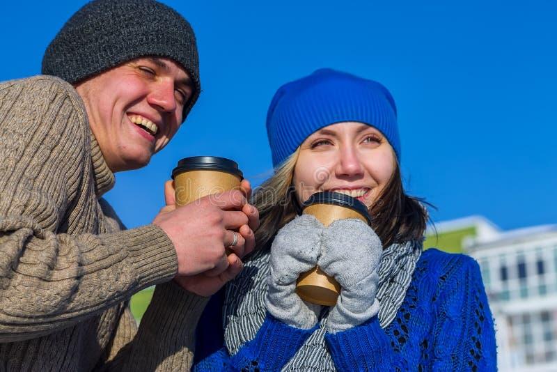 Couples dans le chandail d'hiver étreignant des tasses de café photographie stock