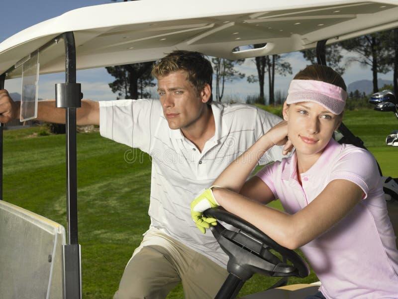 Couples dans le chariot de golf photographie stock libre de droits