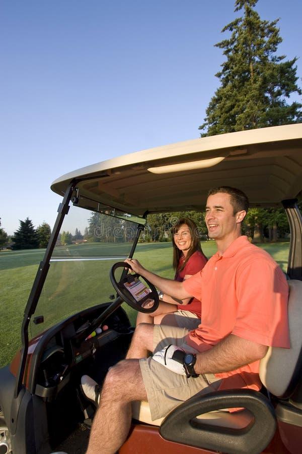 Couples dans le chariot sur le terrain de golf - verticale photos stock