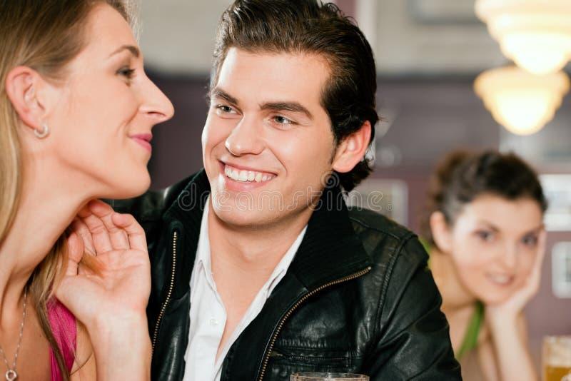 Couples dans le flirt potable de bière de bar photo libre de droits