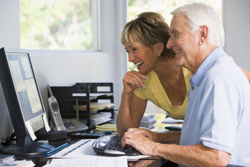 Couples dans le Home Office avec l'ordinateur photos stock