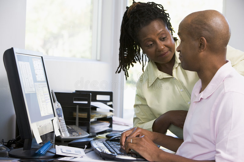 Couples dans le Home Office utilisant l'ordinateur photo stock
