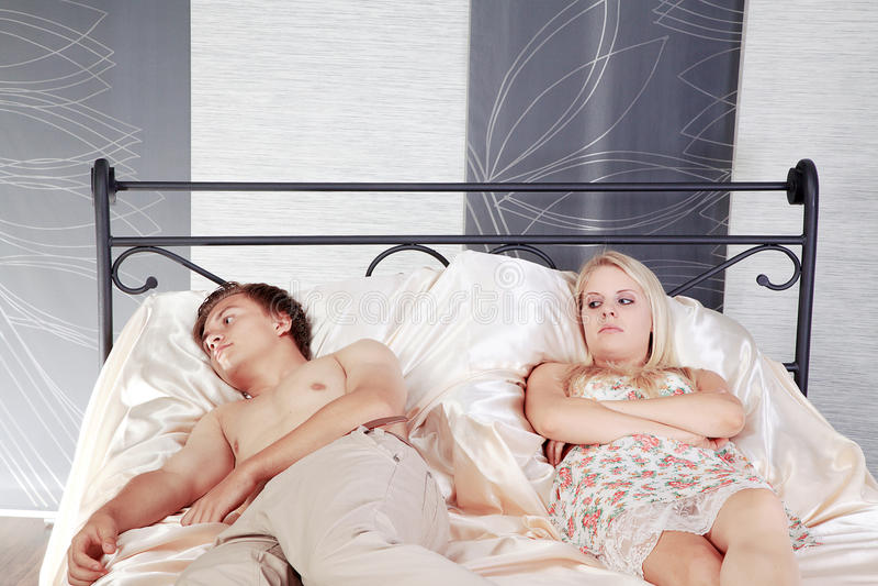 Couples dans le lit et déçus photos stock