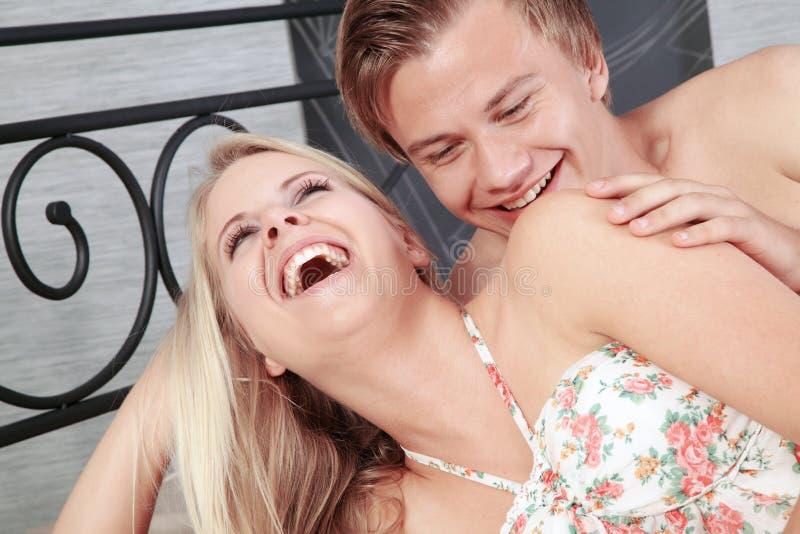 Couples dans le lit et sourire à l'un l'autre image stock