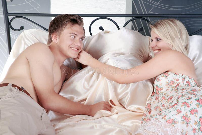 Couples dans le lit et sourire à l'un l'autre images stock