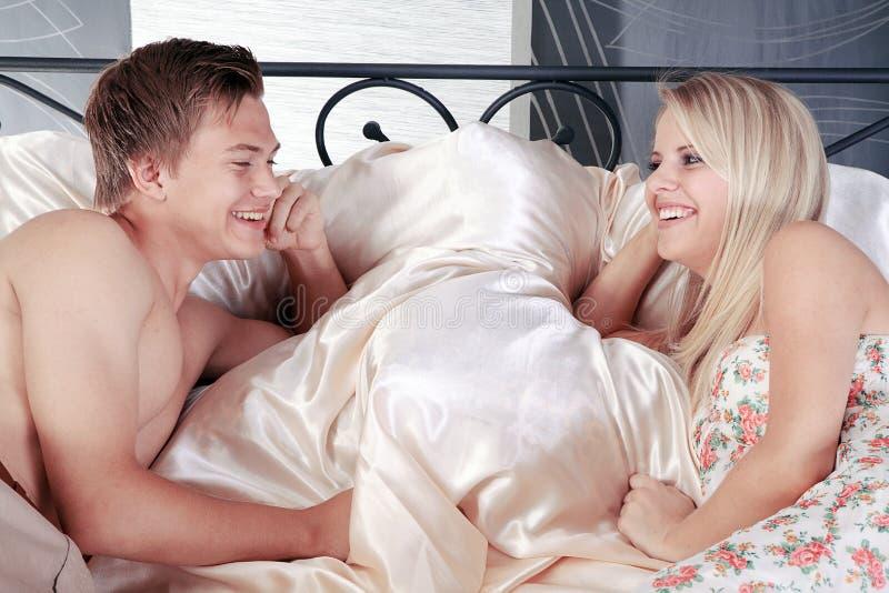 Couples dans le lit et sourire à l'un l'autre photographie stock libre de droits