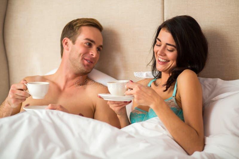 Couples dans le lit tenant des tasses photos libres de droits