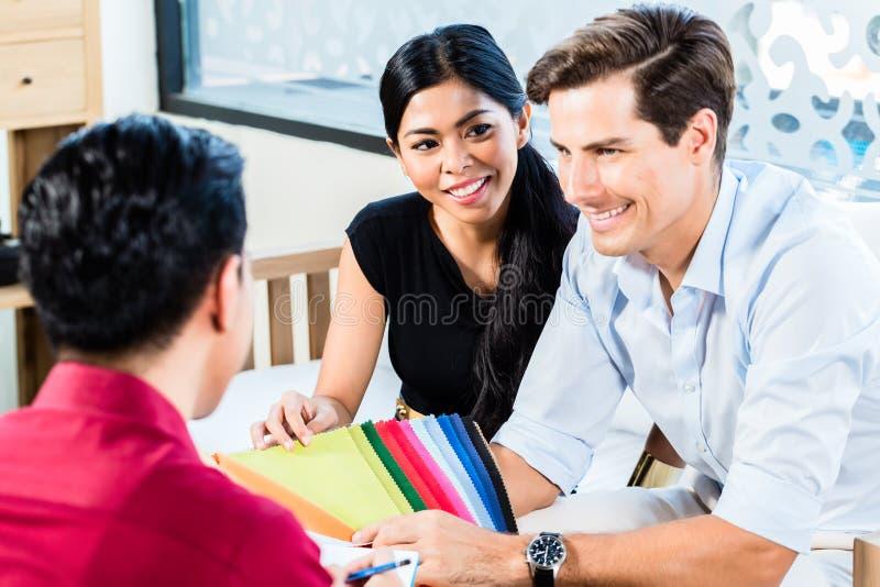 Couples dans le magasin de meubles avec l'employé de magasin image libre de droits