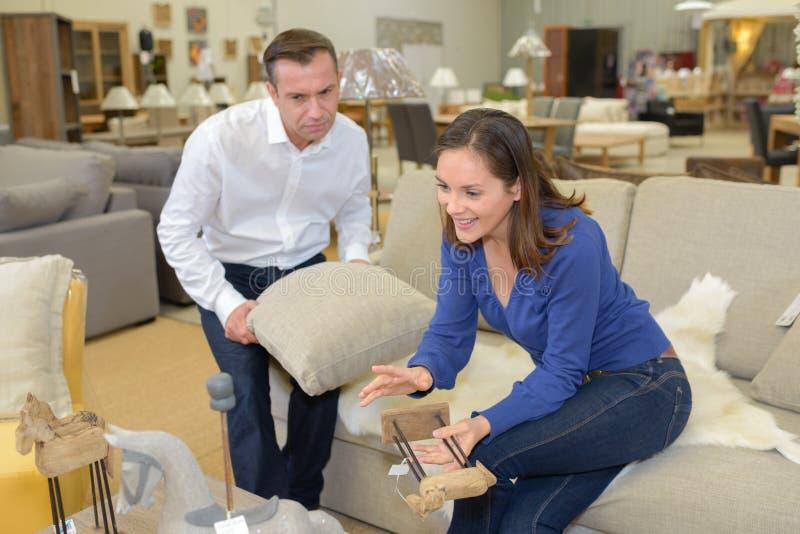 Couples dans le magasin de meubles de sofa photographie stock libre de droits