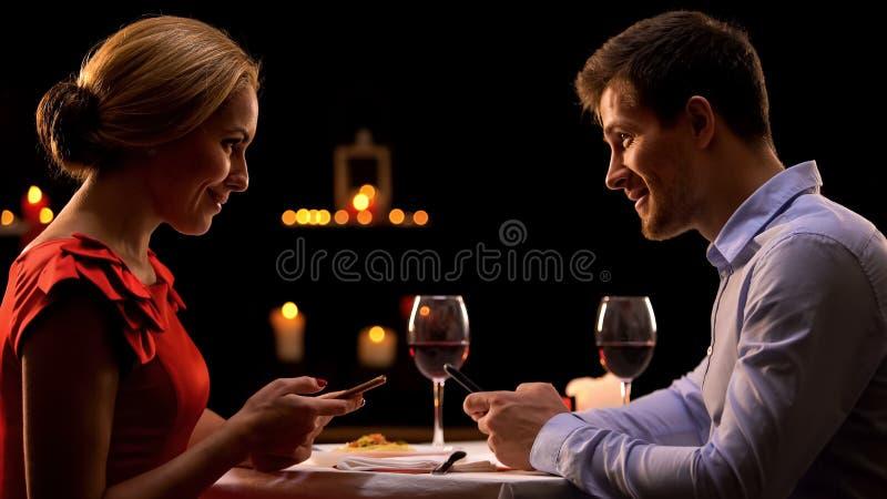 Couples dans le restaurant utilisant des smartphones, datant le concept de site Web, connaissance image libre de droits