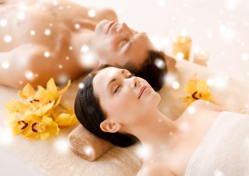 Couples dans le salon de station thermale se trouvant sur les bureaux de massage image stock