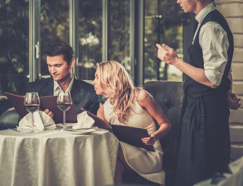 Couples dans un restaurant faisant l'ordre image stock